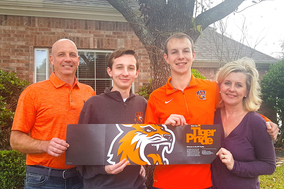 family of four holding an RIT Tiger Pride banner.