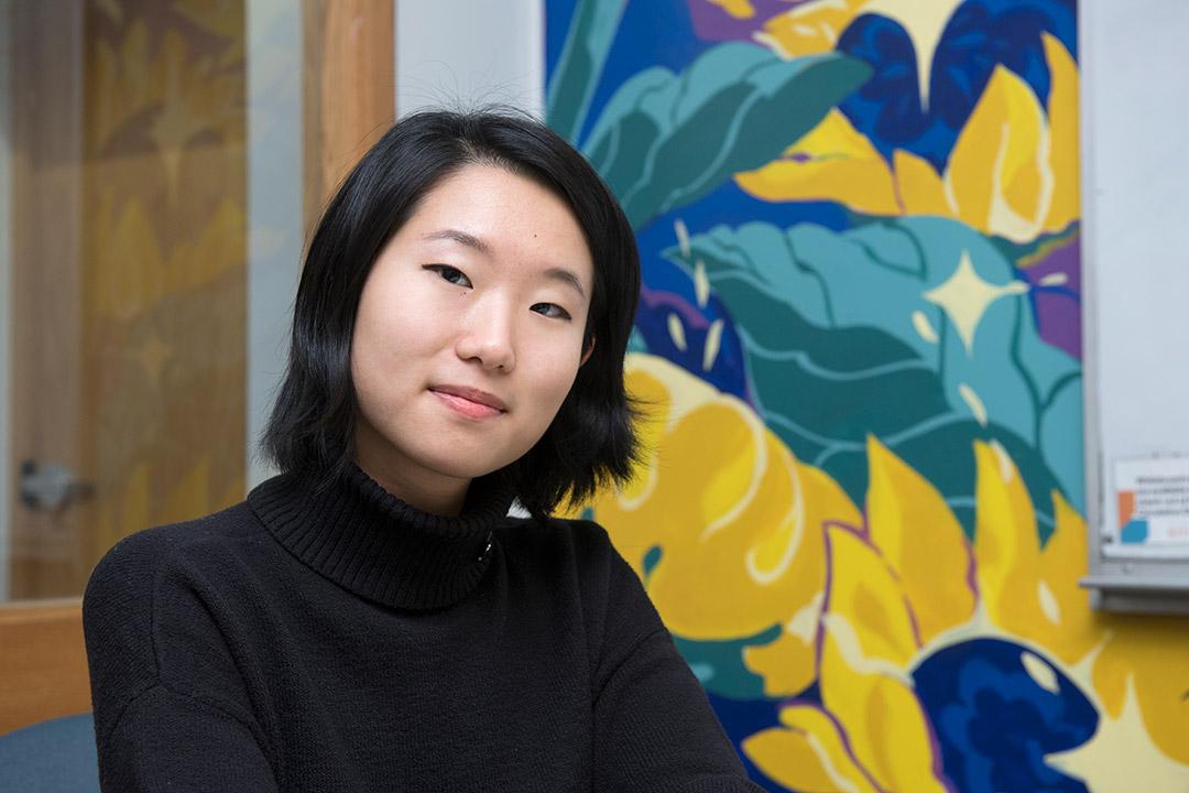 student posing with sunflower-inspired mural artwork.