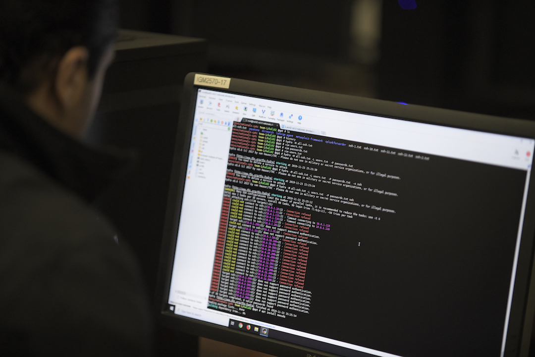 Person looking at multi-colored computer code on a computer monitor.