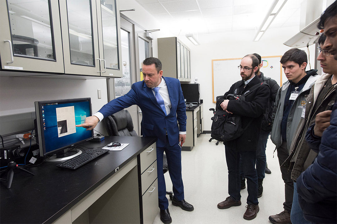 researcher giving demonstration of computer equipment to visitors.