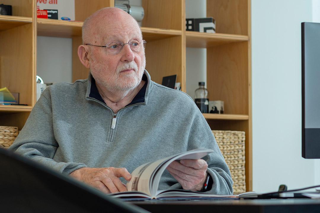 retiring professor looking through magazine on desk.