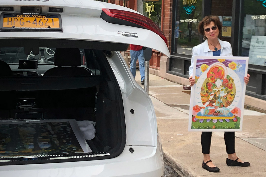 woman holding artwork while standing next to her car.