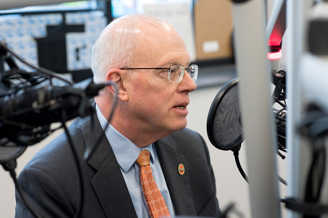 RIT president talking into microphone at radio station.