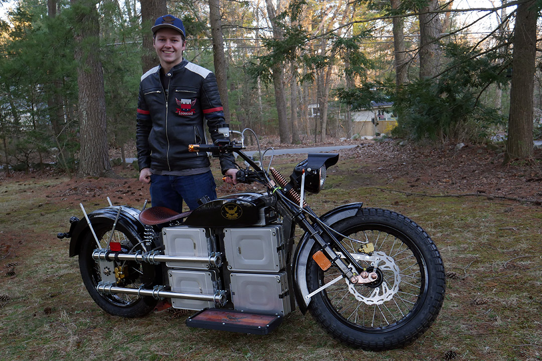student standing with electric motorcycle.