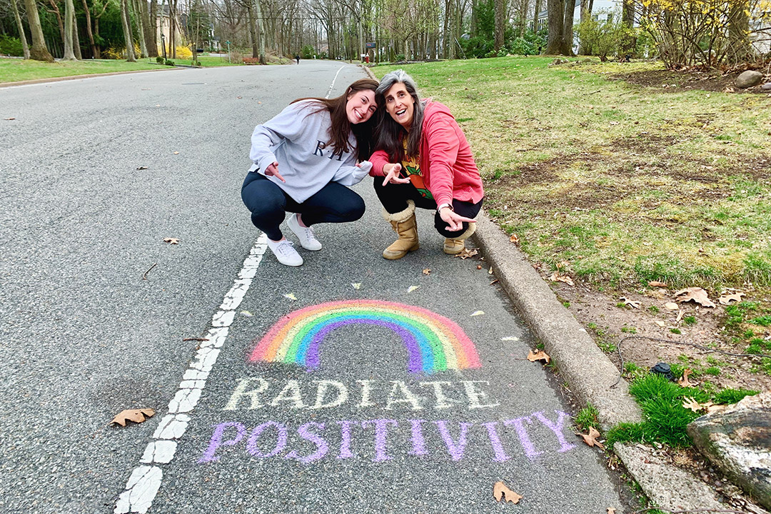 "mother and daughter posing on street above sidewalk chalk art of the words ""radiate positivity"" and a rainbow."
