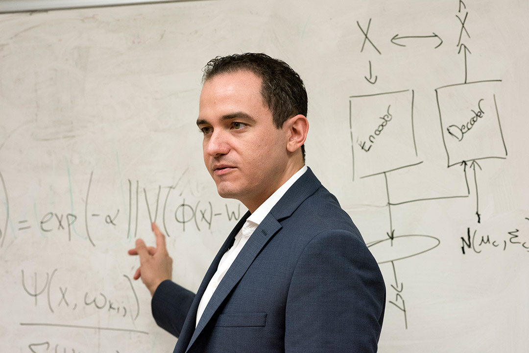 researcher pointing at equations on dry-erase board.