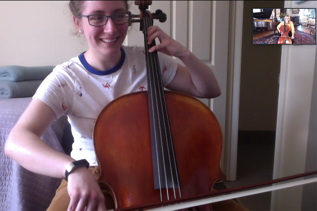 student playing the cello on video conference call with instructor also playing the cello.