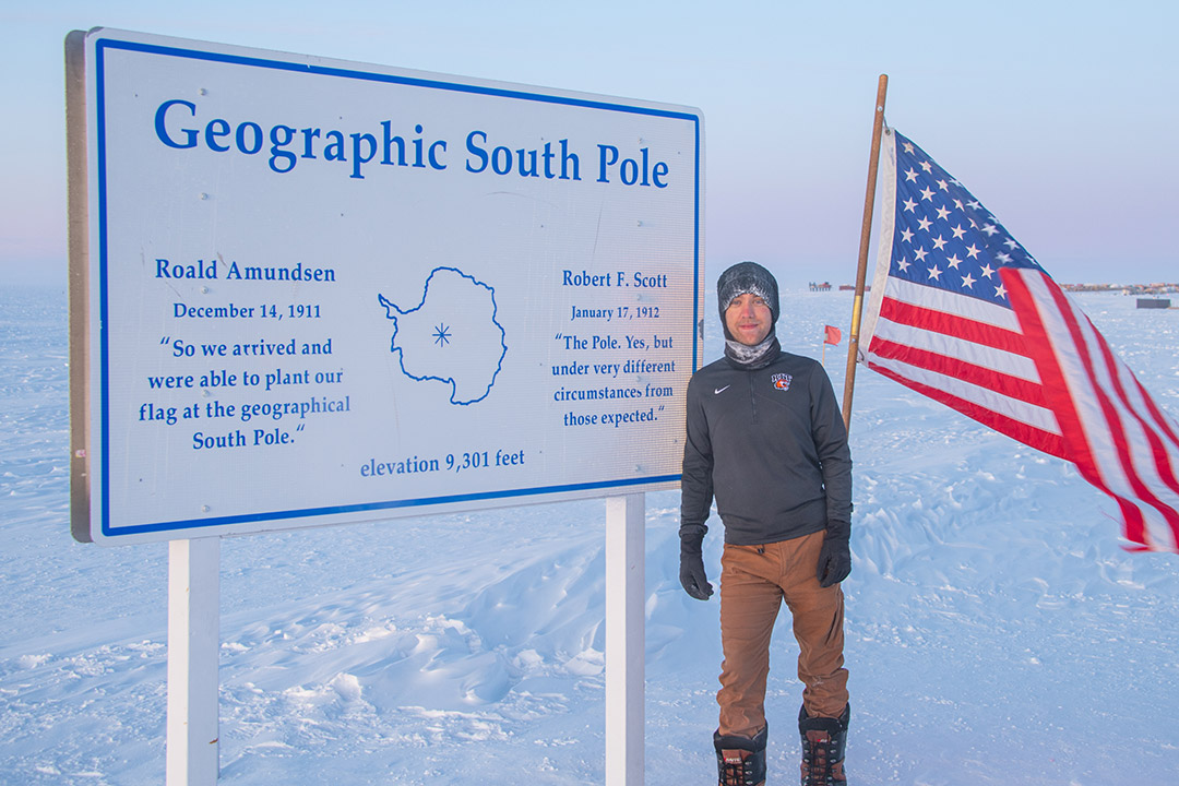 man standing at the geographic south pole with an American flag.