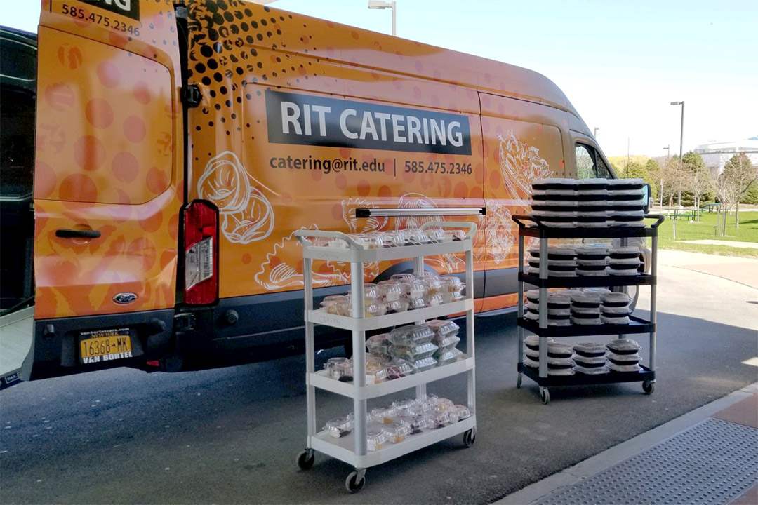 catering van with two racks of boxed meals.