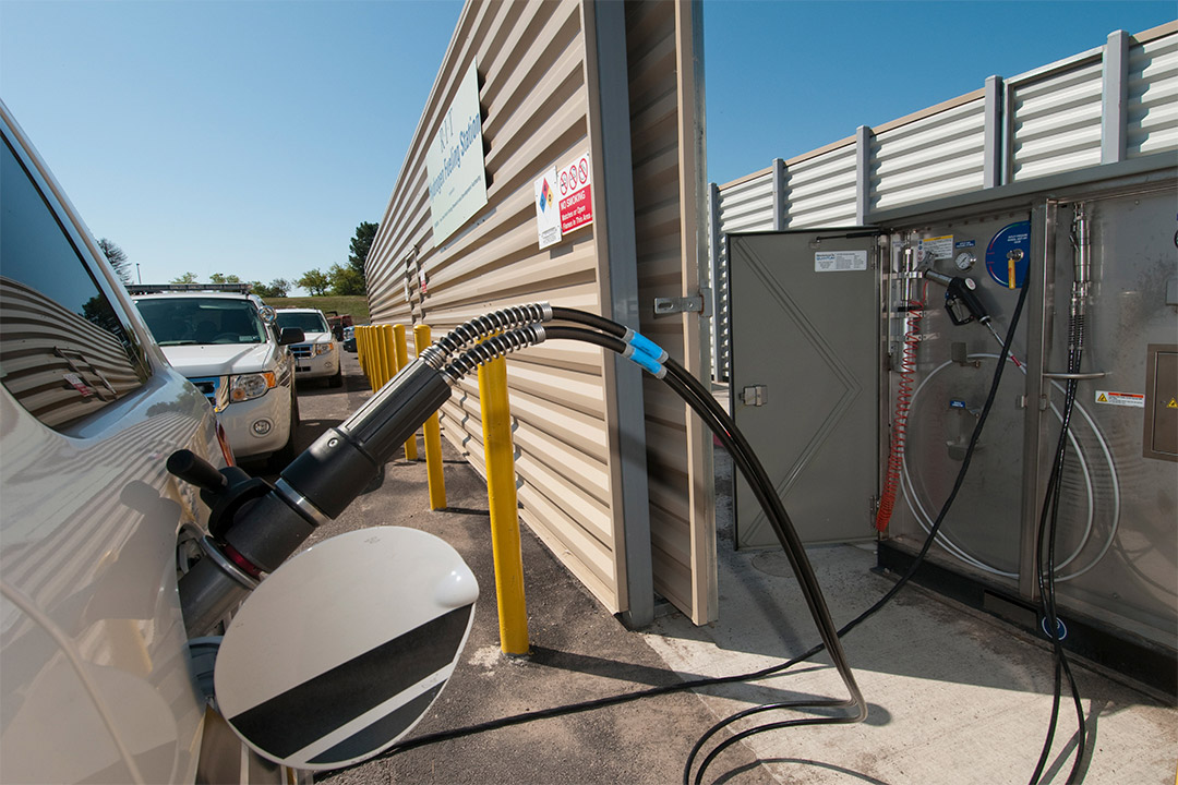 car plugged into hydrogen fueling station.