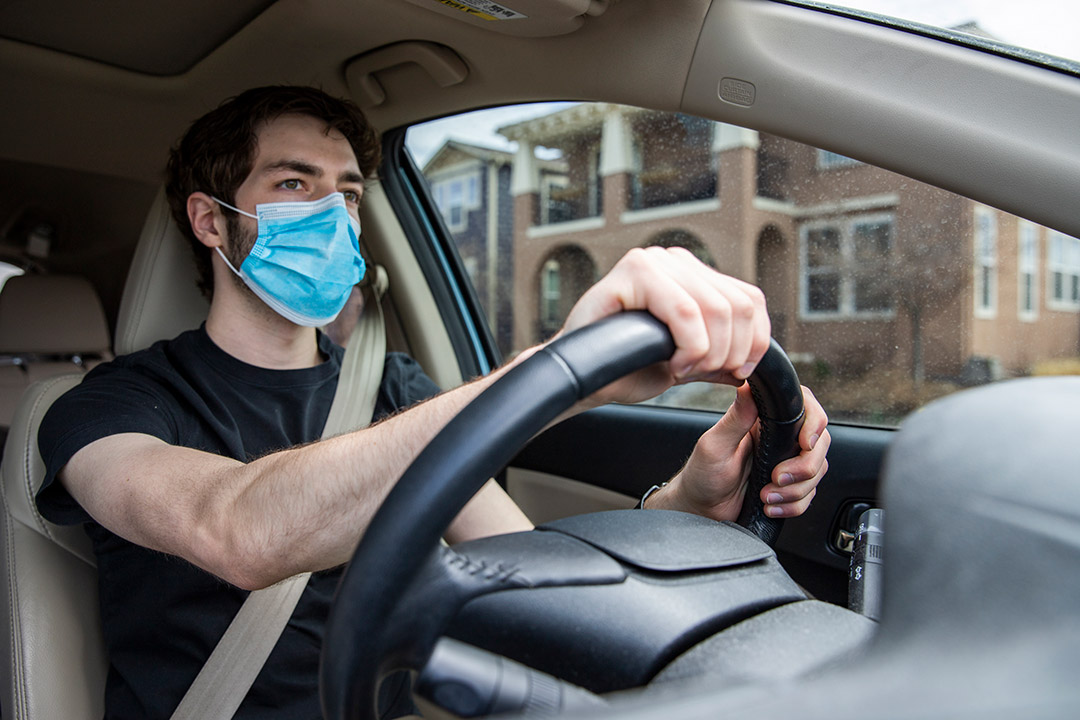 student driving car while wearing face mask.