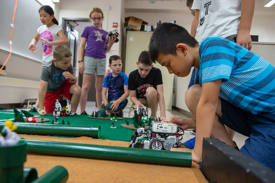 Elementary school children play with small robots they created.