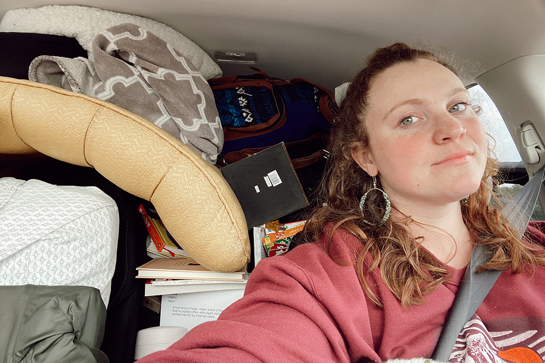 student in driver's seat of car packed with belongings.