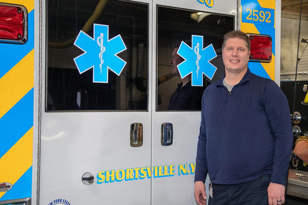 student posing behind Shortsville, N.Y. ambulance.