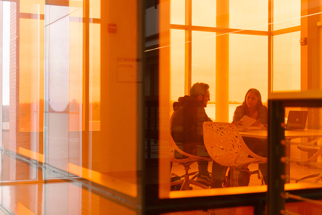 two students working in room with orange-tinted windows.