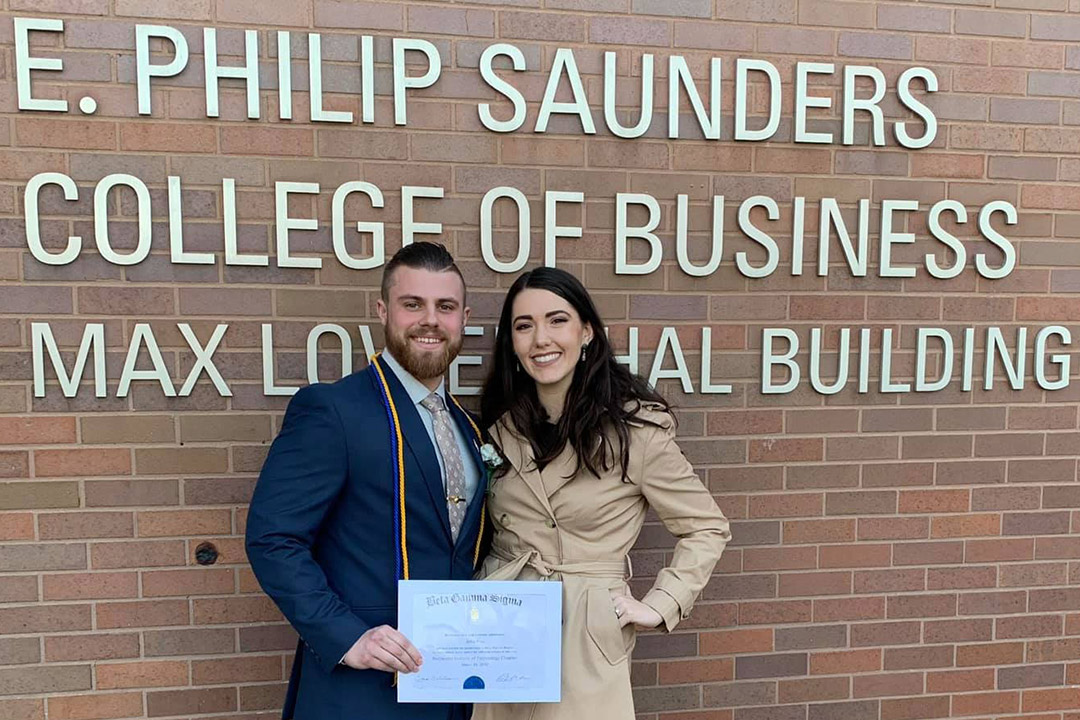 student and fiancee standing in front of exterior of E. Philip Saunders College of Business.