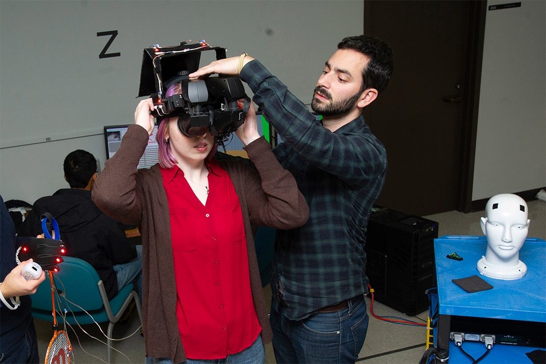 professor helping student put on virtual reality headset.