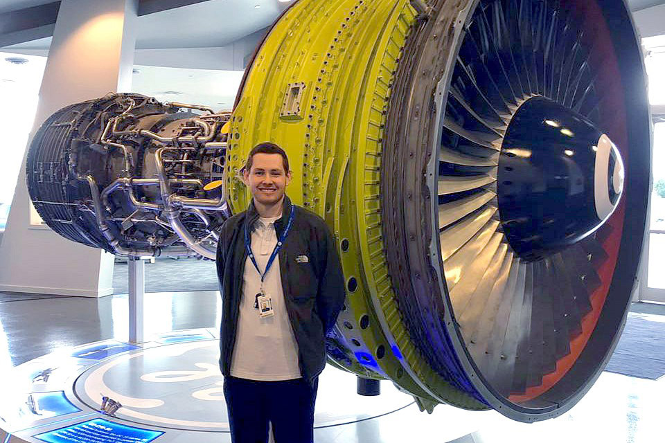 student standing in front of huge jet engine.