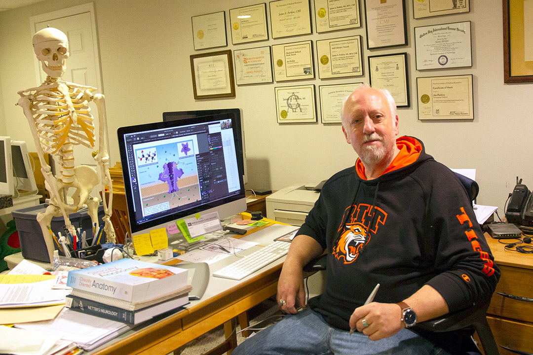 professor posing at desk with certifications and degrees in the background and a human skeleton.
