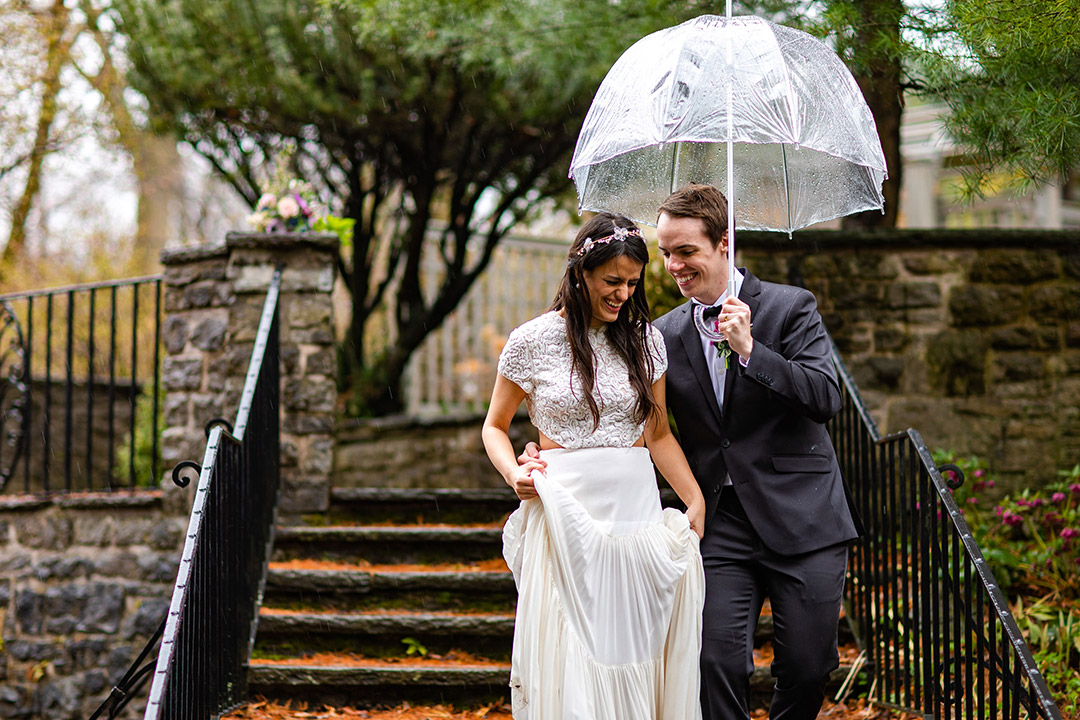 couple getting married poses under umbrella.