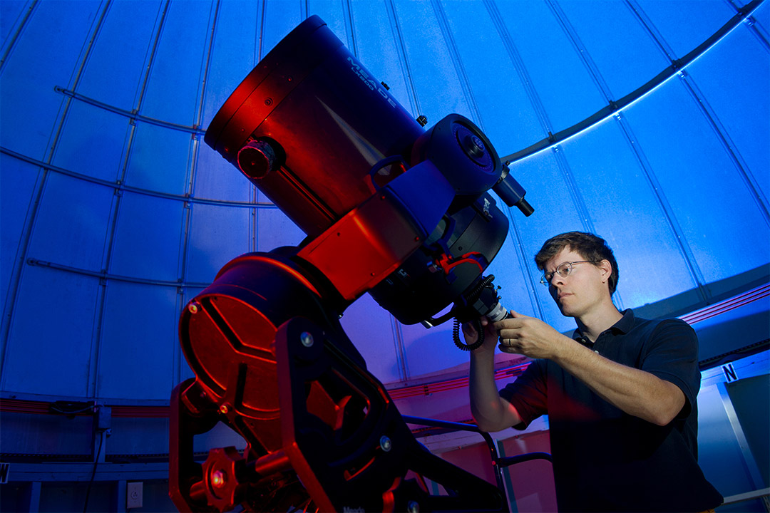 man looking at giant telescope in an observatory.