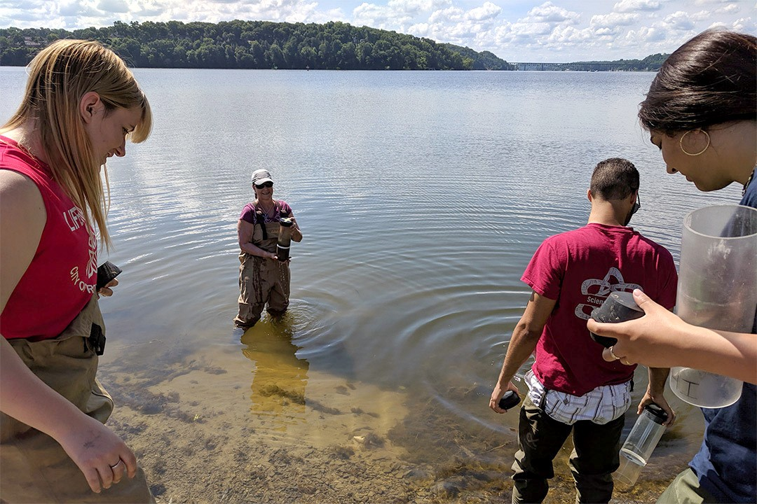 four researchers collecting sediment samples from a lake.
