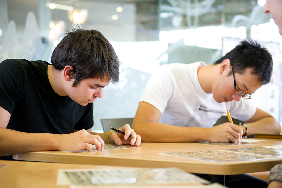 two students filling out a worksheet.