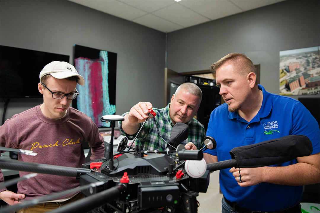 three researchers working on a drone.