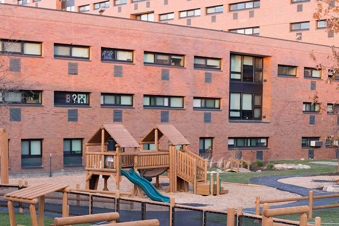 brick building with wooden playground in foreground.