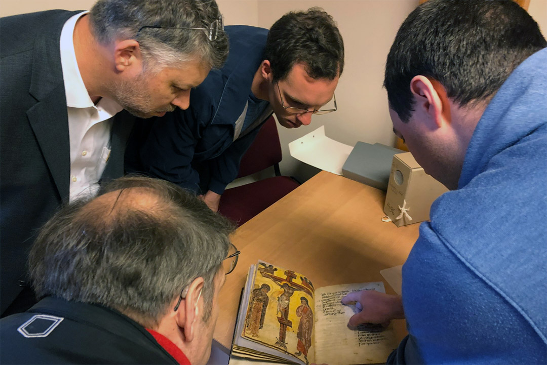 four researchers looking at ancient manuscript.