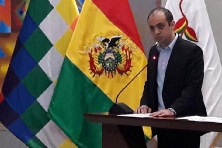 man speaking at podium next to the Bolivian flag.