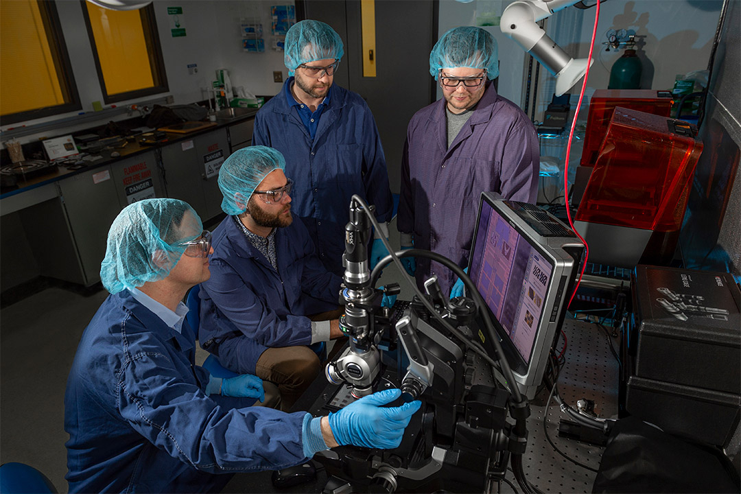 Four scientists analyzing quantum photonics wafer.