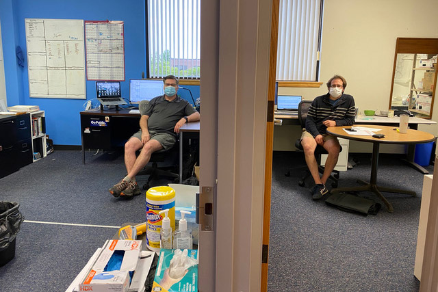 two men sitting in adjacent offices.