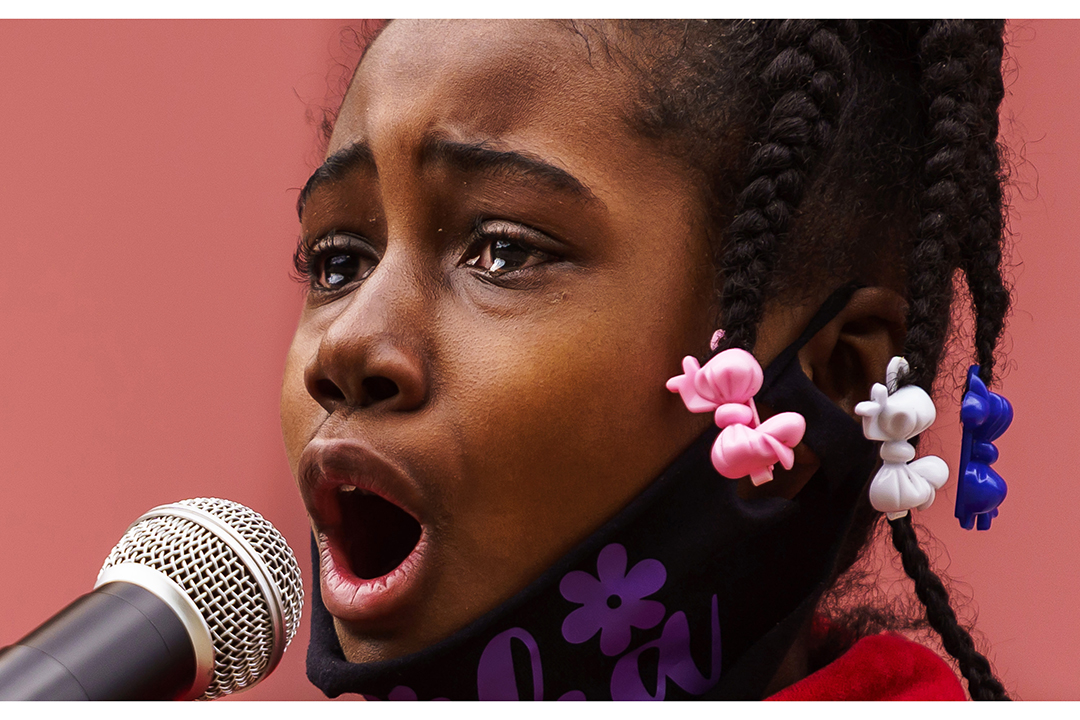 A girl stands behind a microphone, fighting back tears.