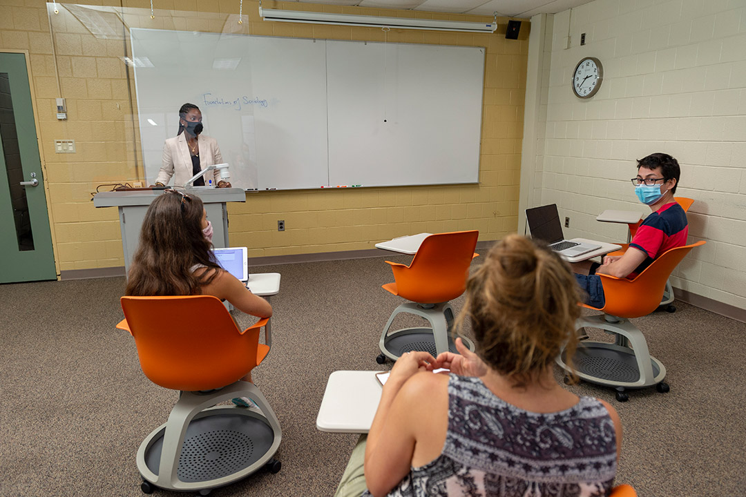 professor wearing a mask stands in the front of a classroom behind a plexiglas barrier as three students sit six feet apart.