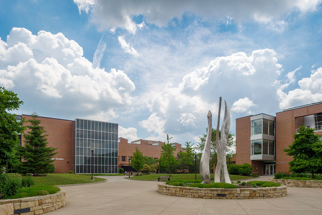 outside of RIT campus, featuring brick and glass buildings and a metal sculpture.