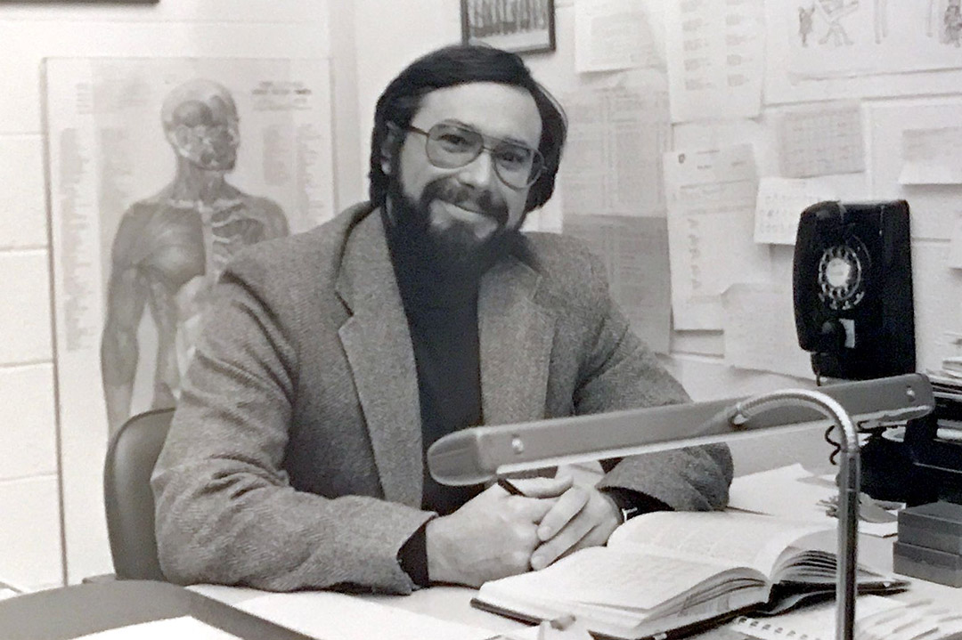 professor sitting at his desk in the 1980s.