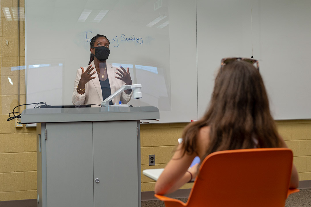 professor teaching from podium behind a plexiglas barrier.