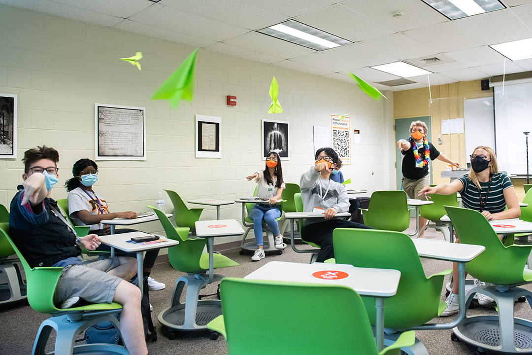 students in a classroom throwing paper airplanes.