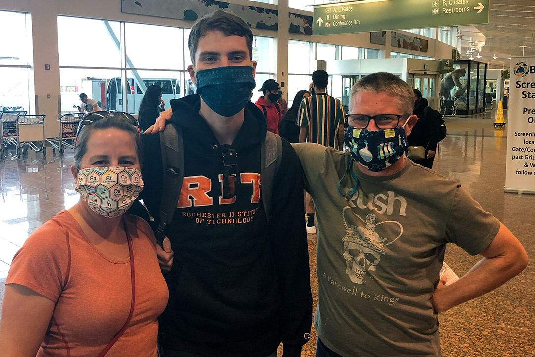 family of three standing in an airport wearing face masks.