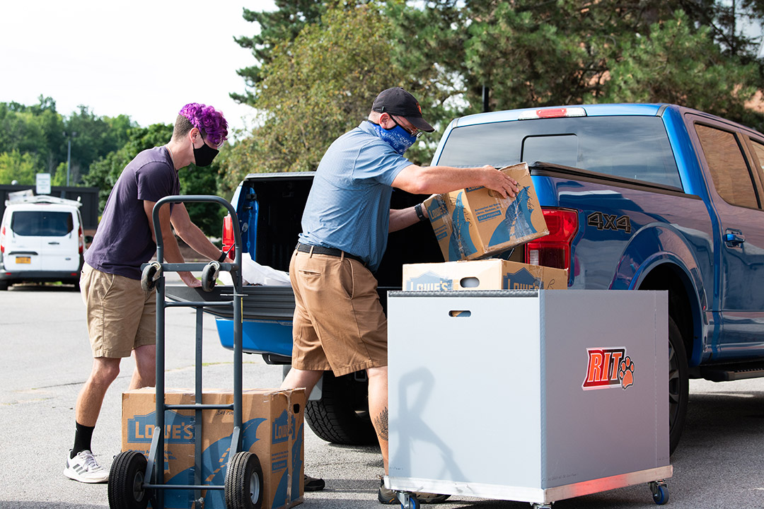 student and parent unloading pickup truck to move in to campus housing.