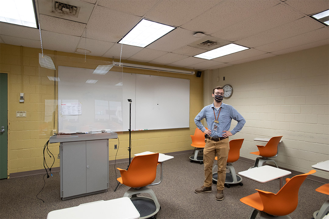 student worker standing in classroom with plexiglas hanging from ceiling.