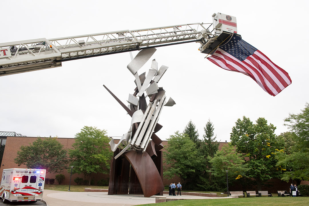 firetruck ladder extended over campus statue with large American flag flying from the bucket.