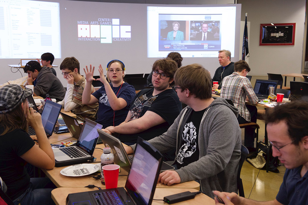 Students gathered at tables working together with computers.