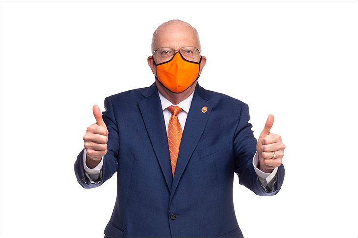 President Munson wearing an orange face mask and giving two thumbs up.