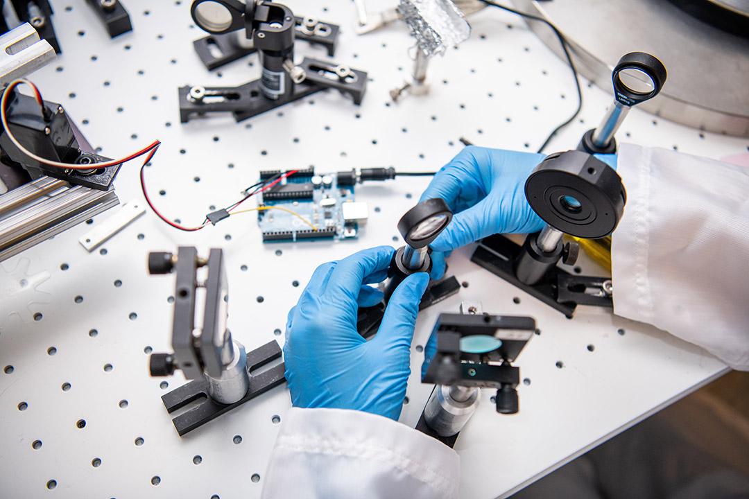 gloved hands adjusting setup of varying magnifying lenses.