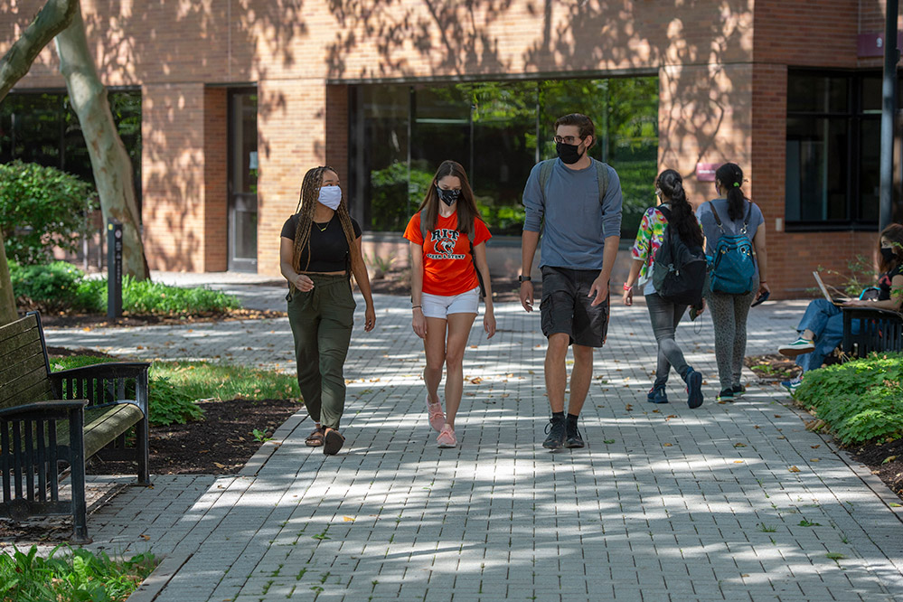 students walking outside wearing masks.