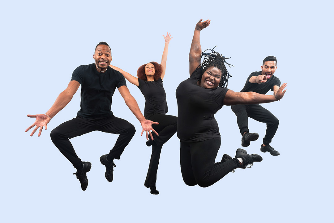 theater troupe wearing all black and jumping in the air.