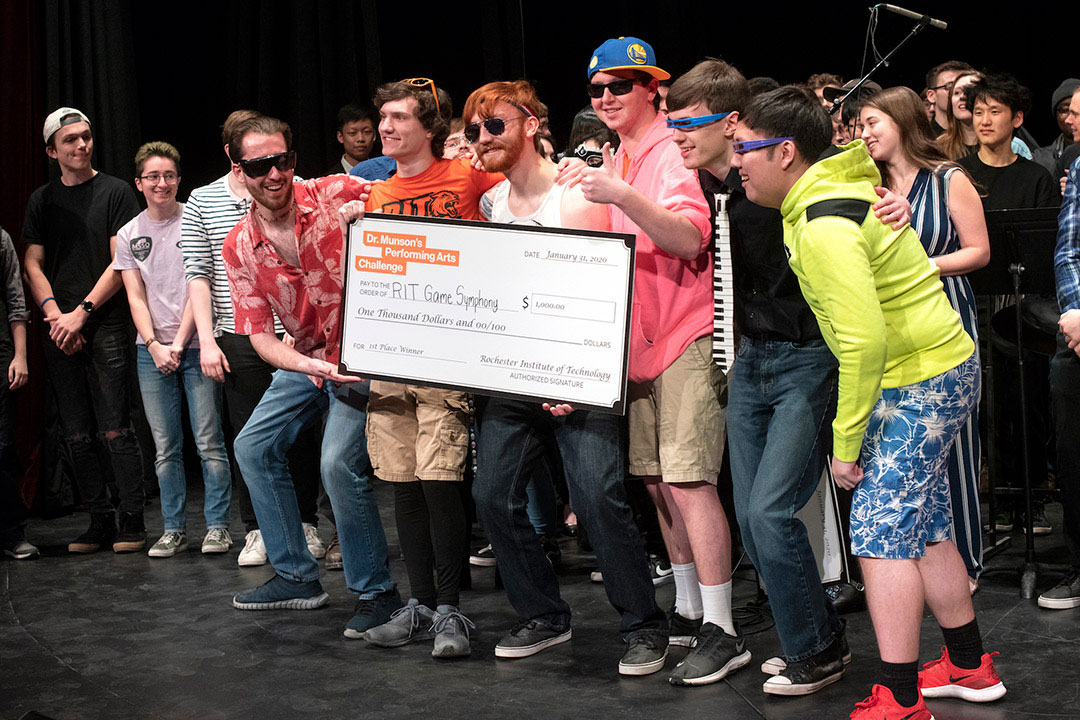 group of students on a stage holding a giant novelty check.