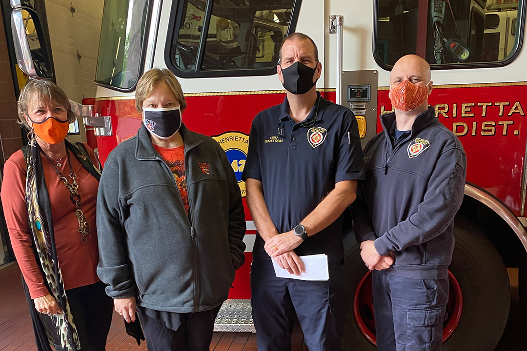 four people wearing masks standing next to a firetruck.